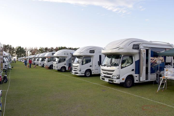 キャンプ大会でキャンピングカーが並ぶイメージ